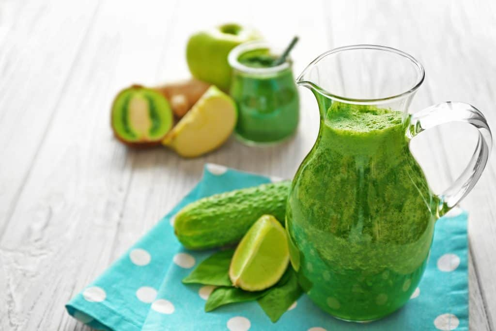 Green smoothie drink with fruit on table